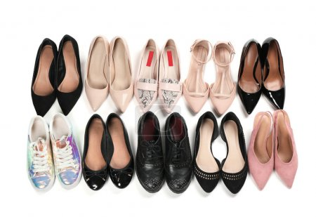 Various female stylish shoes on white background, top view