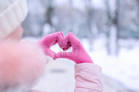 Photo for Closeup view of cute girl showing heart with hands outdoors. Winter vacation - Royalty Free Image