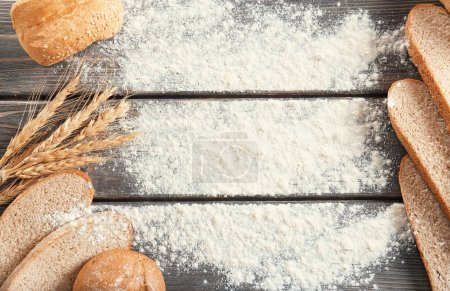 Freshly baked bread products and flour on wooden background