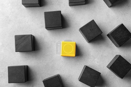 One yellow cube standing out from others on light background. Think different concept