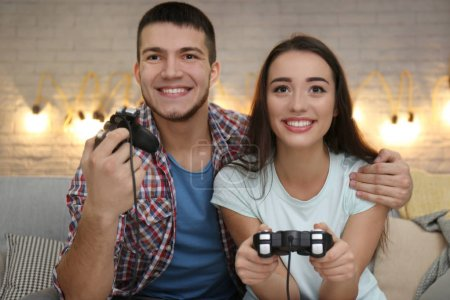 Photo for Young couple sitting on sofa and playing video game at home - Royalty Free Image