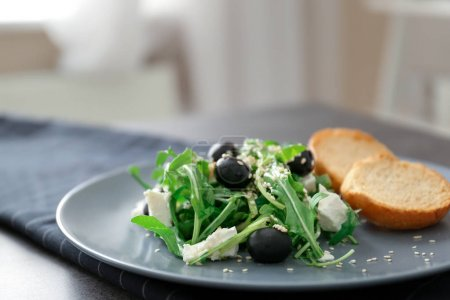 Salad with olives and arugula leaves, closeup