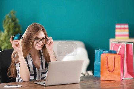 Photo pour Jeune femme, shopping en ligne avec carte de crédit et ordinateur portable à la table - image libre de droit