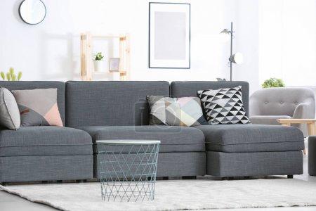 Foto de Moderno sofá gris con diferentes almohadas en la sala de estar - Imagen libre de derechos
