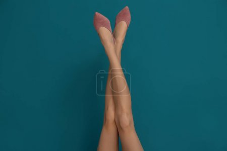 Photo for Legs of beautiful woman in stylish shoes on color background - Royalty Free Image