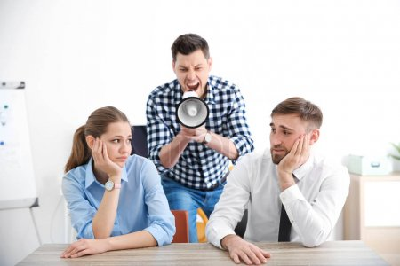 boss with megaphone screaming at employees
