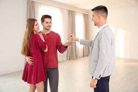 Real estate agent giving house key to young couple indoors