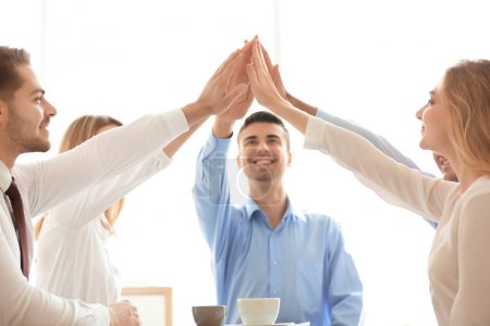 Photo for Young people in office wear putting hands together on light background. Unity concept - Royalty Free Image
