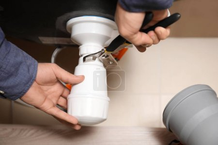 Professional male plumber replacing sink trap, closeup