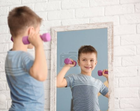 Cute little boy with dumbbells posing in front of mirror indoors