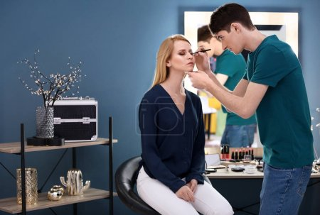 Photo for Professional makeup artist working with young model in salon - Royalty Free Image