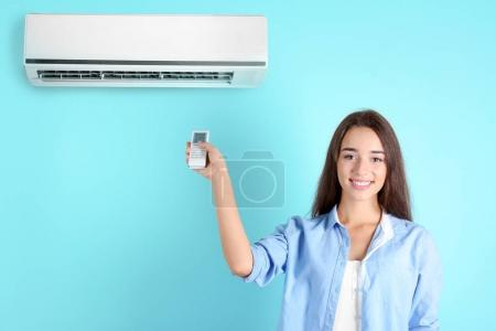woman switching on air conditioner