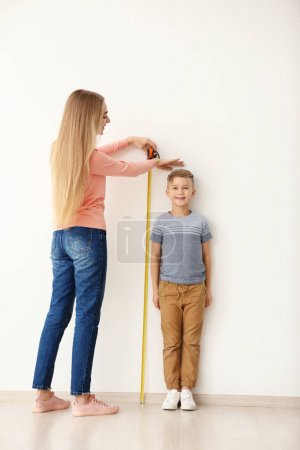 woman measuring height of little boy