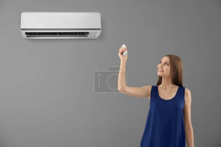Young woman switching on air conditioner against color background