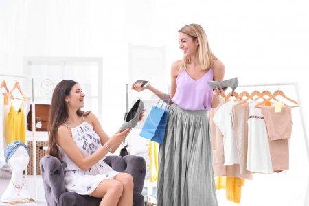 Young beautiful women choosing shoes while shopping in store