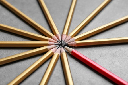 One red pencil among golden ones on gray background. Difference and uniqueness concept