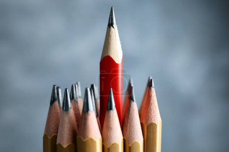 Photo pour Un crayon rouge parmi les dorés sur fond flou. Concept de différence et d'unicité - image libre de droit