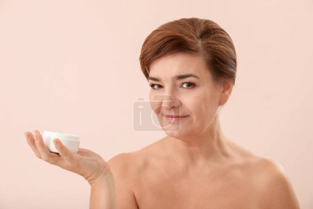 Portrait of beautiful mature woman with jar of anti-aging cream on light color background. Skin care concept