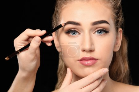 Young woman undergoing eyebrow correction procedure on dark background