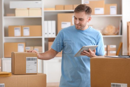 Photo for Young man with tablet computer preparing parcels for shipment to client in home office - Royalty Free Image