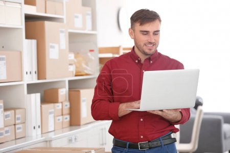 Photo for Young man with laptop preparing parcels for shipment to client in home office - Royalty Free Image