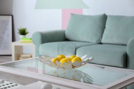 Photo for Decorative plate with apples on table near comfortable sofa indoors - Royalty Free Image