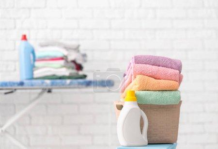 Photo pour Panier avec serviettes propres et détergent à lessive à la maison - image libre de droit