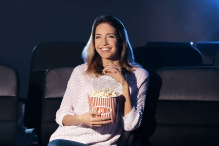 Young woman with popcorn watching movie in cinema