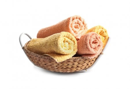 Wicker basket with clean terry towels on white background
