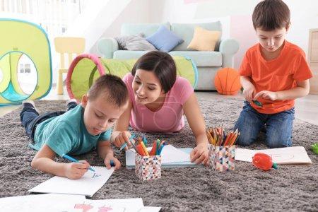 Photo pour Deux petits garçons de dessin avec nounou à domicile - image libre de droit