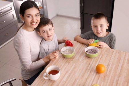 Photo pour Nounou alimentation mignons petits garçons dans cuisine - image libre de droit