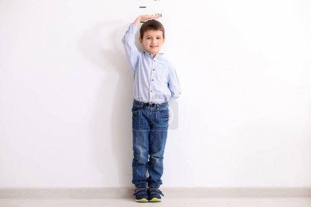 Little boy measuring height near white wall