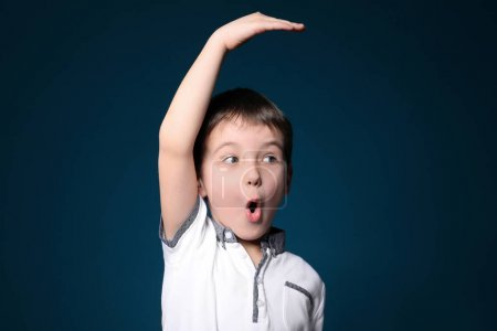 Little boy measuring height on color background