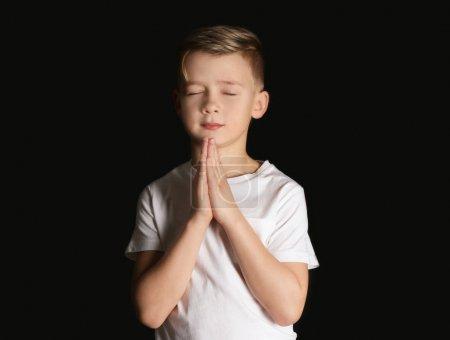 Religious little boy praying on black background
