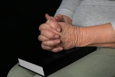 Religious elderly woman praying over Bible, closeup
