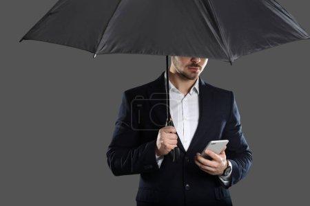 junger Mann mit Regenschirm und Smartphone auf grauem Hintergrund