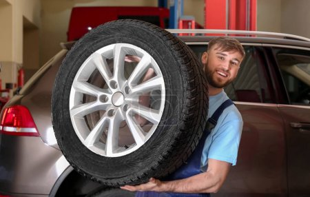 Mechanic with car wheel in repair shop. Tire service
