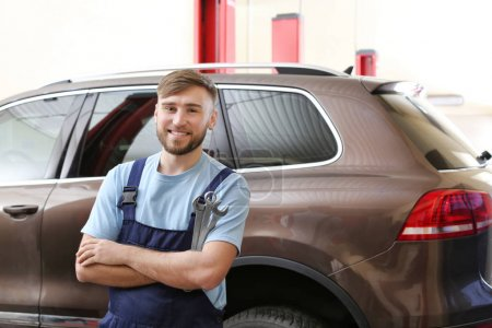 Mechanic with tools in garage. Tire and other car services