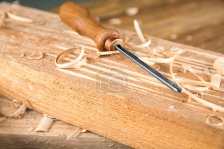 Chisel, wooden boards and sawdust in carpenter's workshop