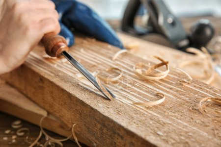 Carpenter working with chisel, closeup