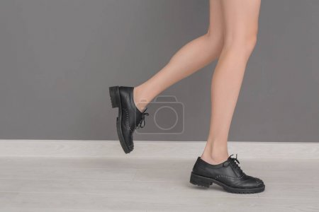 Legs of young woman in stylish shoes standing near gray wall