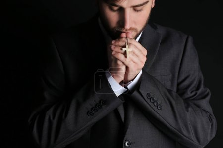 Religious young businessman praying