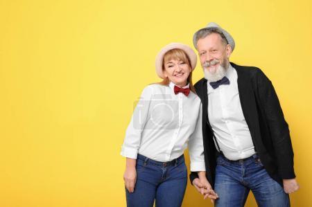 Photo pour Heureux couple aîné en tenues hipster sur fond de couleur - image libre de droit