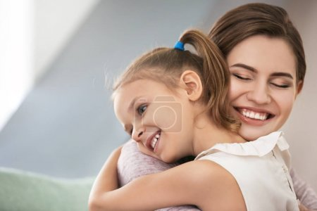 Photo for Portrait of happy mother and daughter hugging at home - Royalty Free Image