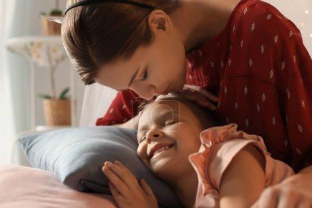 Photo pour Mère embrassant sa fille endormie mignonne à la maison - image libre de droit
