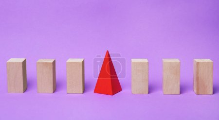 Wooden blocks and one different on color background
