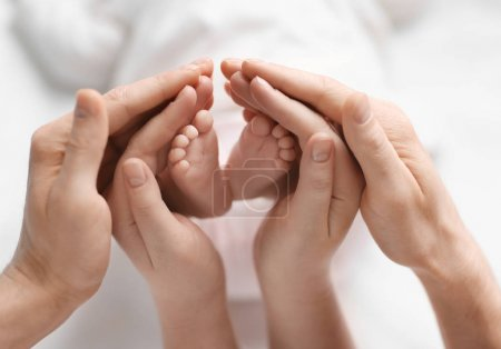 Photo for Young parents holding feet of their baby in hands - Royalty Free Image