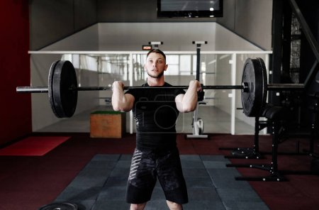 Fit young  athlete lifting the barbell in gym, cop...
