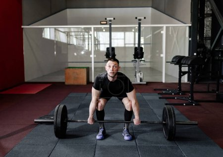 Photo for Fit young  athlete lifting the barbell in gym. Gym training - Royalty Free Image