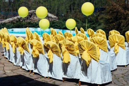 Photo pour Chaises pour les invités à la cérémonie de mariage avec chiffon satin blanc et jaune près de la piscine avec gros ballons en plein air - image libre de droit